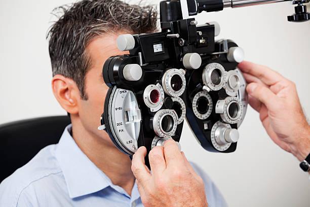 Man having his eyes examined with machine stock photo