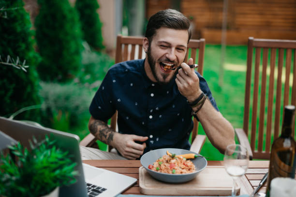 Man having lunch in a garden on a sunny summer day stock photo