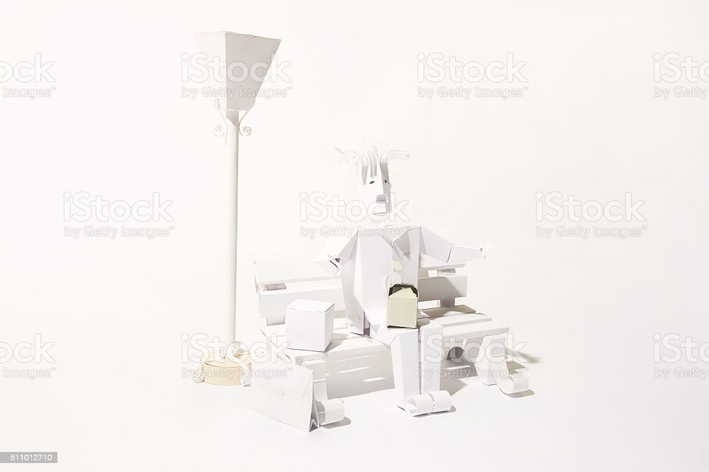 Man having lunchat park cut out of paper stock photo