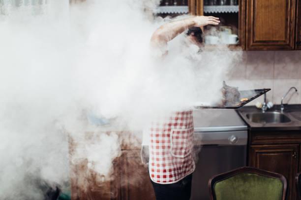 man having problems preparing dinner - burned oven imagens e fotografias de stock