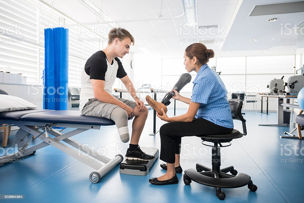 Man having prosthetic leg fitted by physiotherapist stock photo