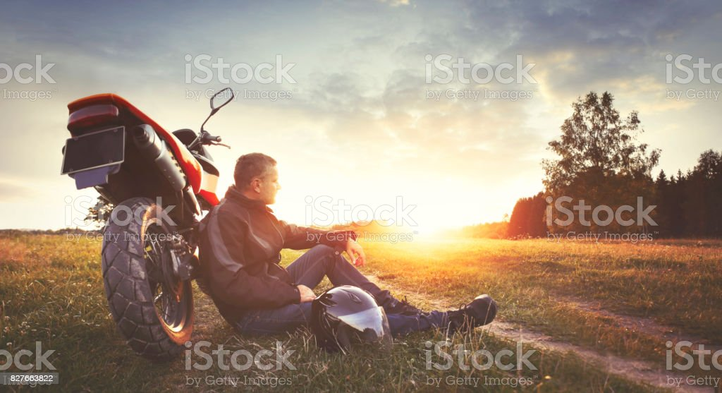 Man having rest in the countryside during motorbike trip stock photo