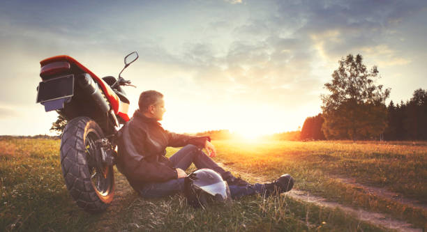 man having rest in the countryside during motorbike trip - motorcycle stock photos and pictures