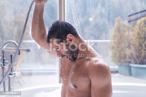 Man having shower in a hot tub with a forest view