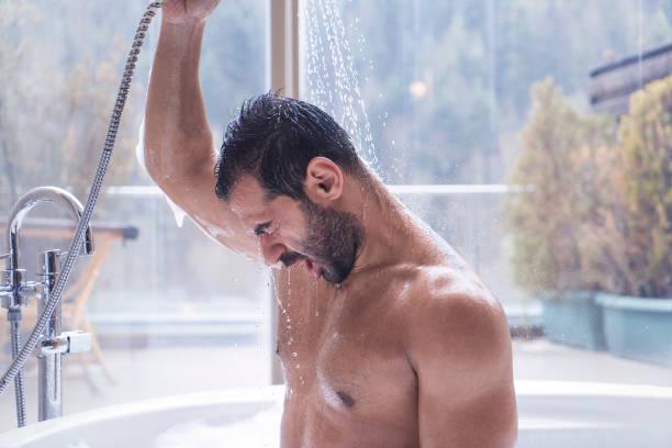 man met douche in een jacuzzi met uitzicht op het bos - douche stockfoto's en -beelden