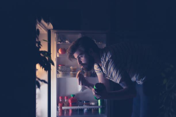 Hombre tener bocado y bebiendo cerveza de noche delante de la nevera - foto de stock