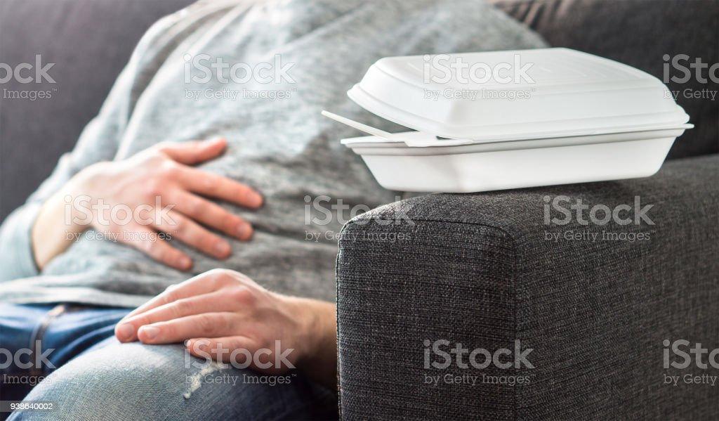 Hombre teniendo problema de dolor o de la digestión estomacal. Patata del sofá, persona perezosa o desempleado tomar siesta. Sentirse mal después de comer demasiada comida basura rápida. - foto de stock