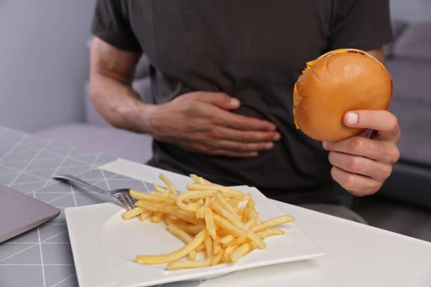 homem tendo dor de estômago por causa de comer junk food de unthelthy. gastrite crônica ou úlcera. - junk food - fotografias e filmes do acervo