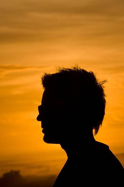 mann steht kopf silhouette von einem hintergrundbeleuchtung bei sonnenuntergang. - elemi stock-fotos und bilder