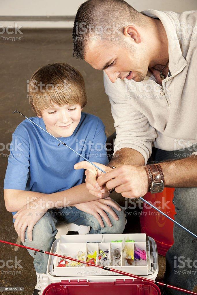 Jovem Adulto homem ajudando menino adolescente com equipamento de pesca - foto de acervo
