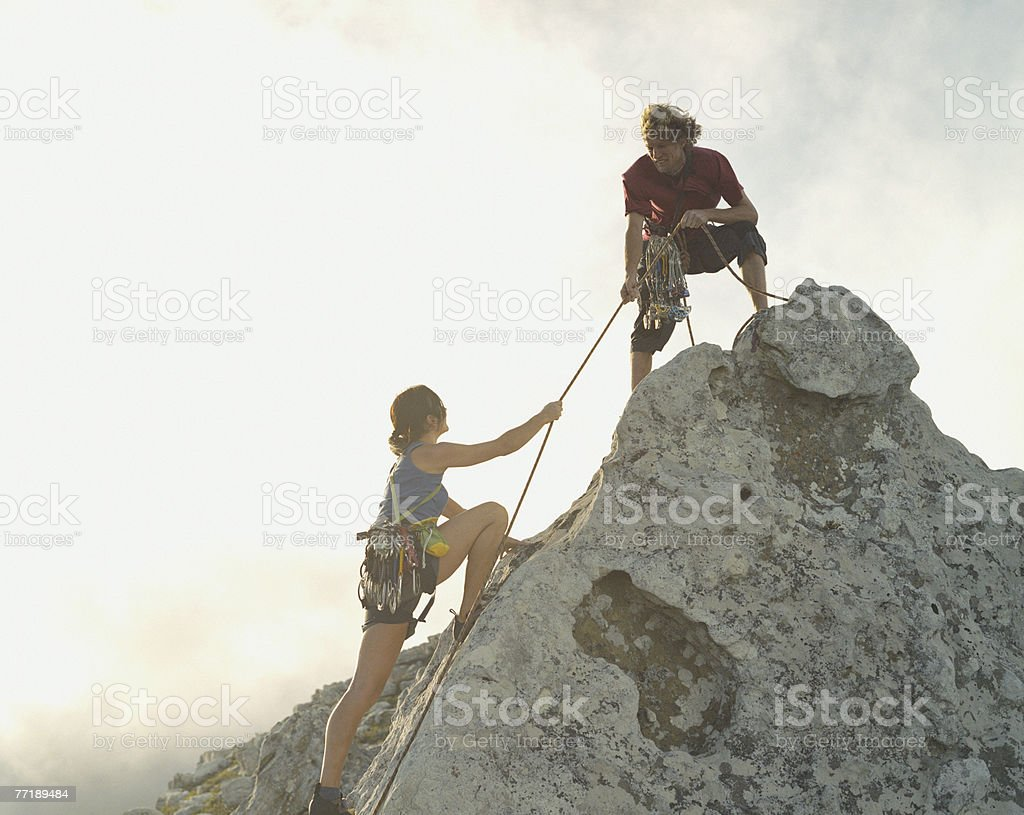 A man helping a woman climber to the top of the mountain stock photo
