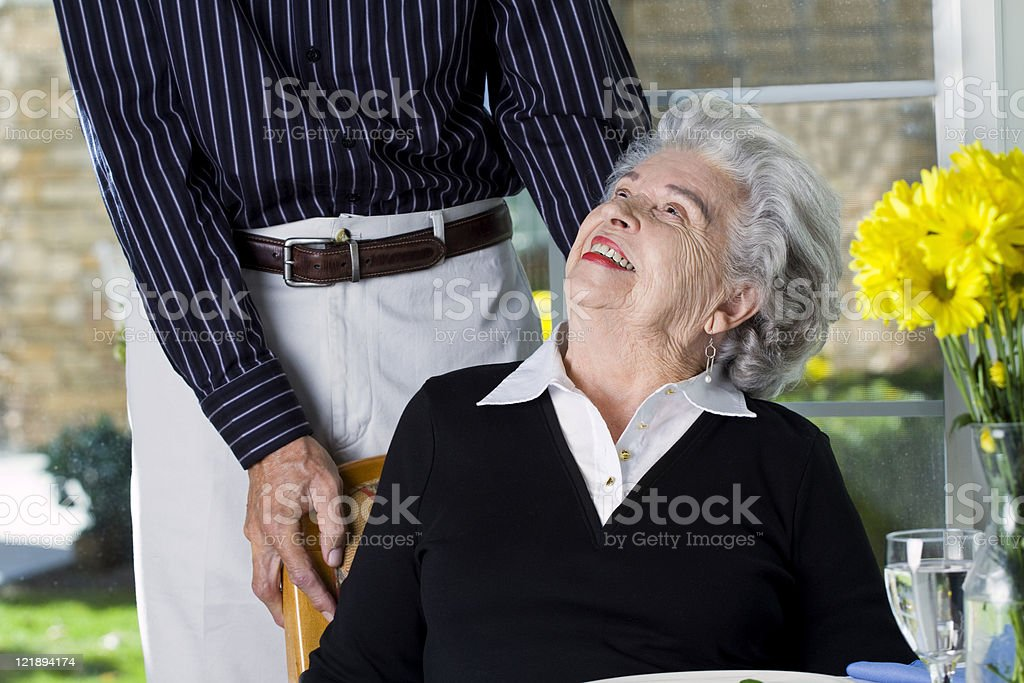 Man Helping a Woman Into Her Chair royalty-free stock photo