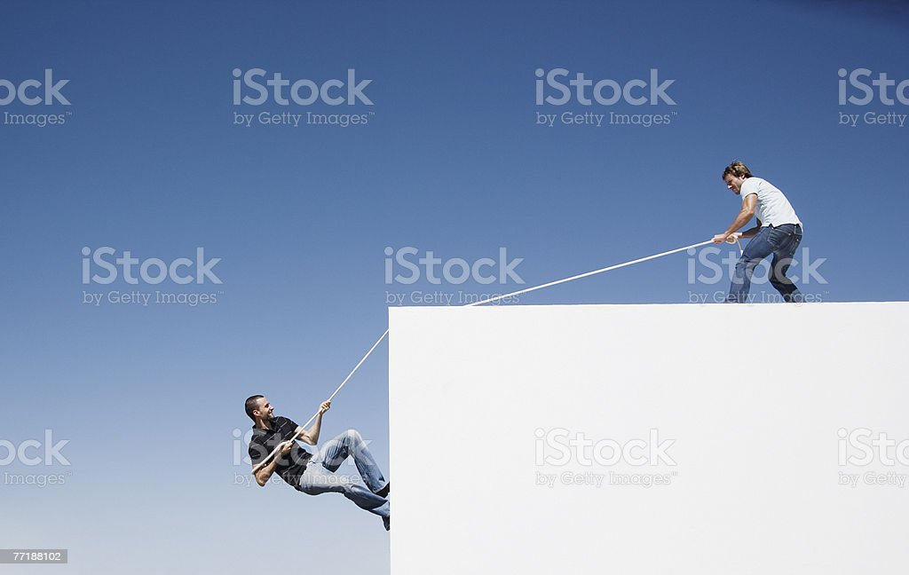 A man helping another man climb up a wall stock photo
