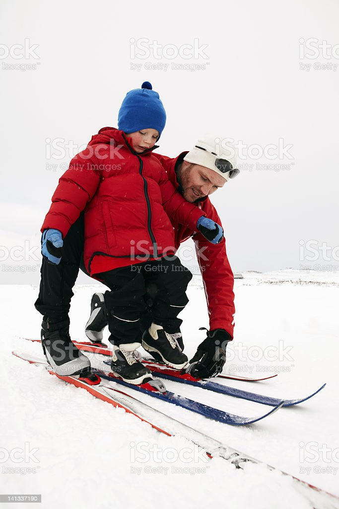 Man helping child put on skis in snow stock photo