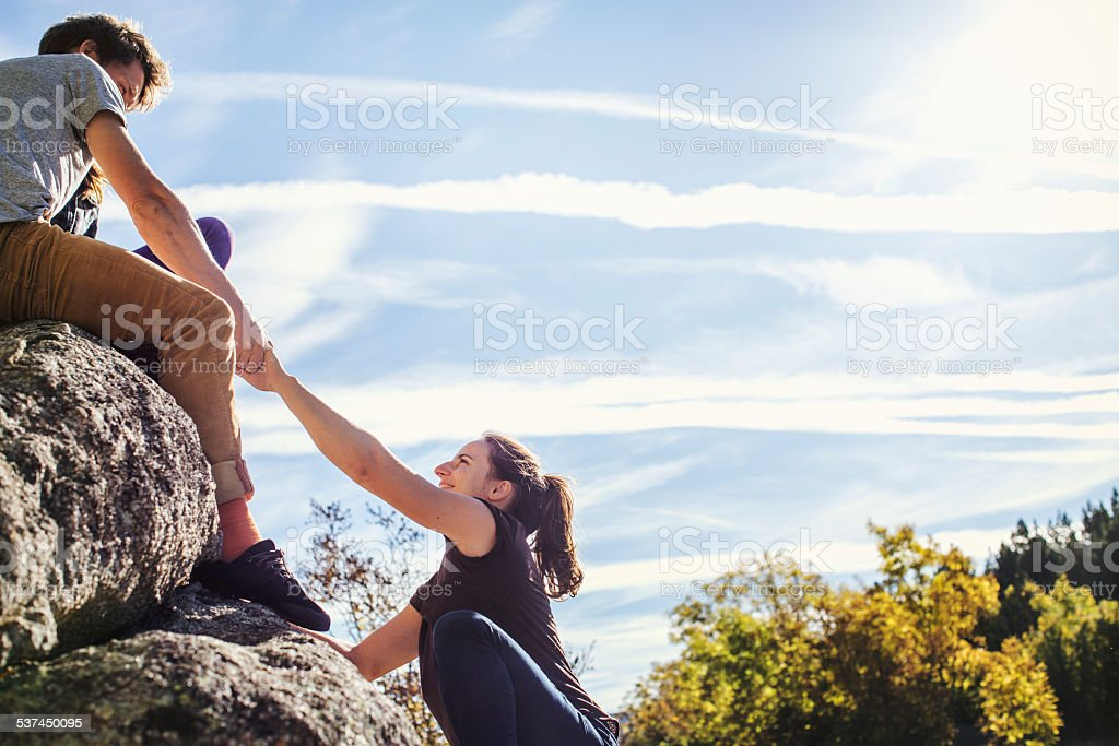 Man helping female friend to climb rock stock photo
