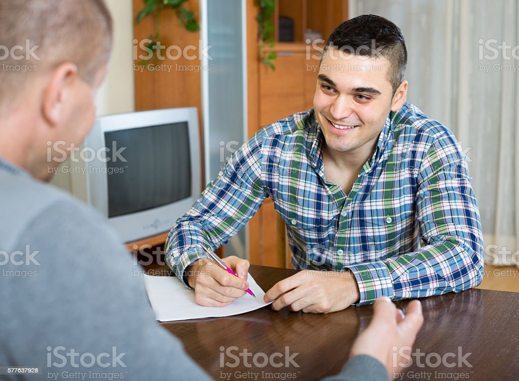Man helping friend to fill document indoor stock photo