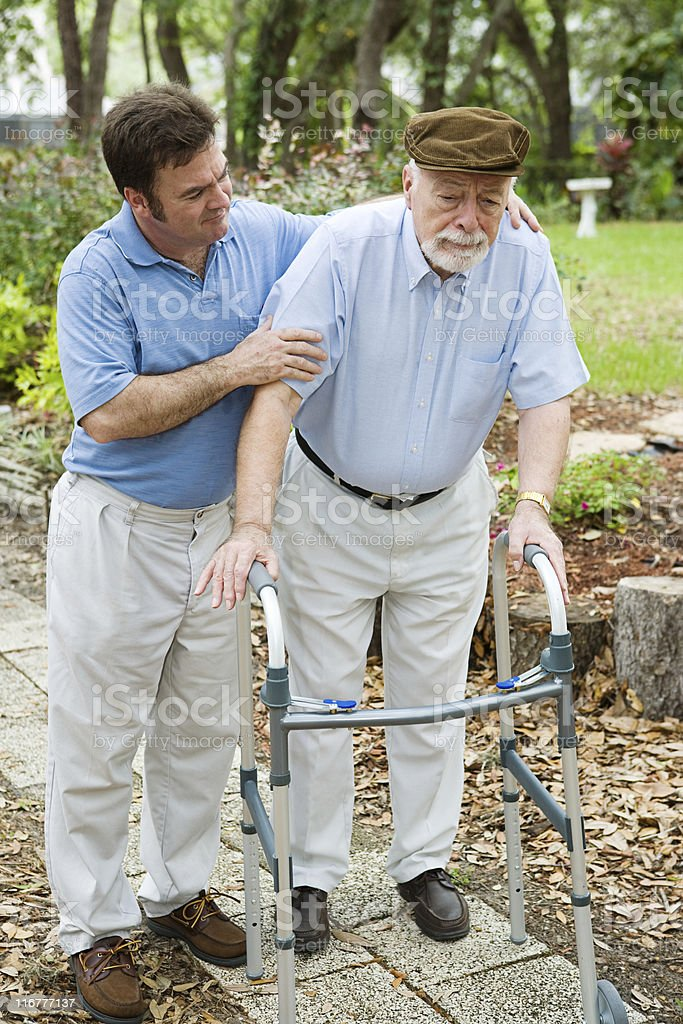 A man helping his elderly father walk stock photo