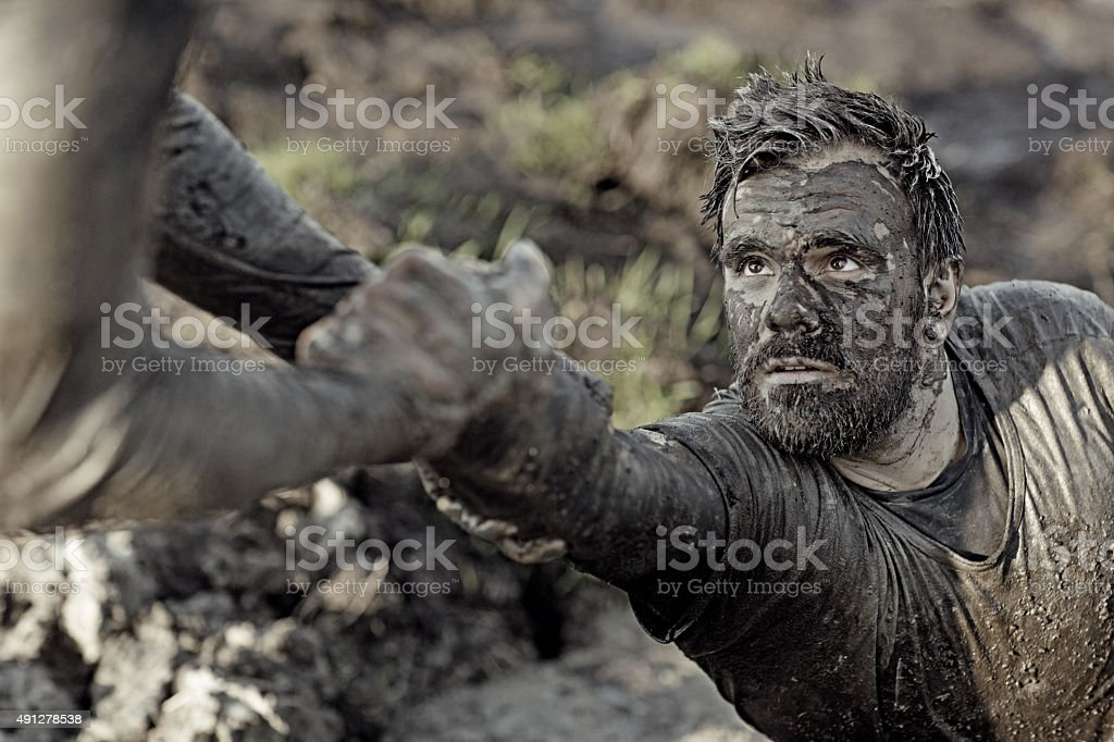 man helping his friend with getting out of mud stock photo
