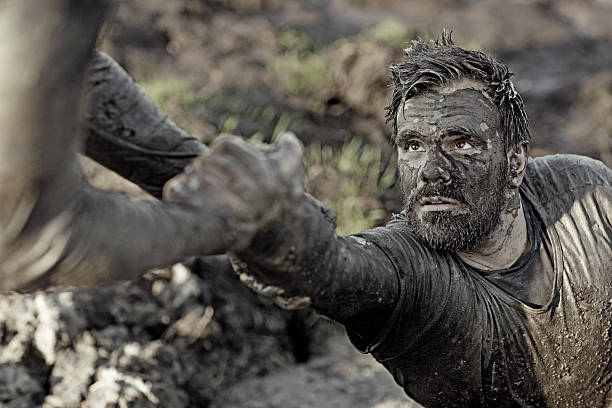 man helping his friend with getting out of mud man helping his friend with getting out of mud obstacle course stock pictures, royalty-free photos & images
