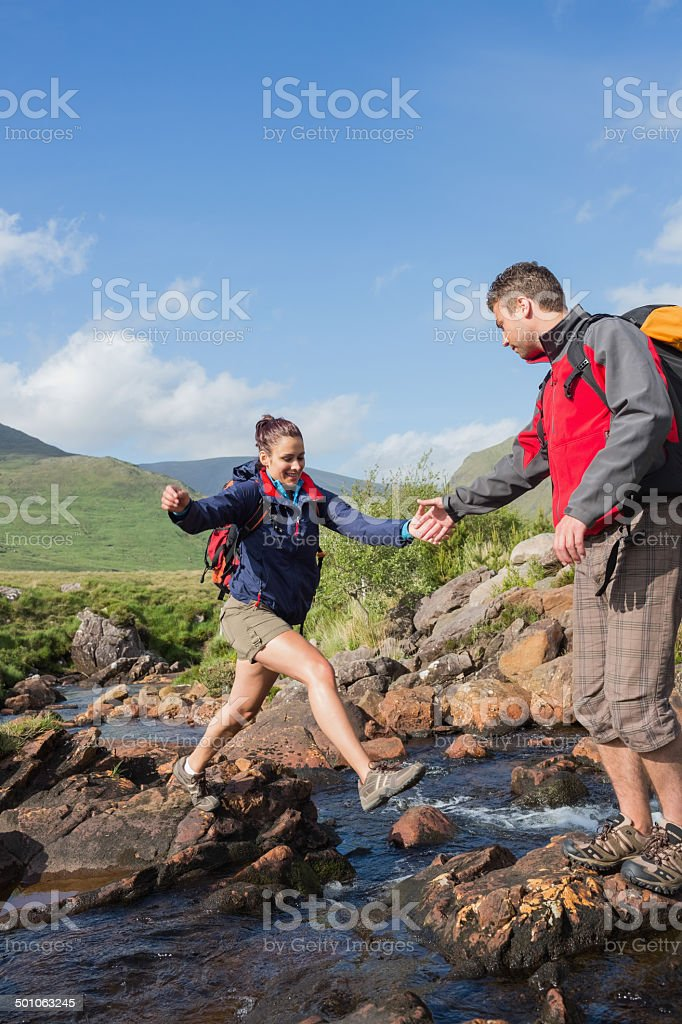 Man helping his girlfriend to cross a stream stock photo