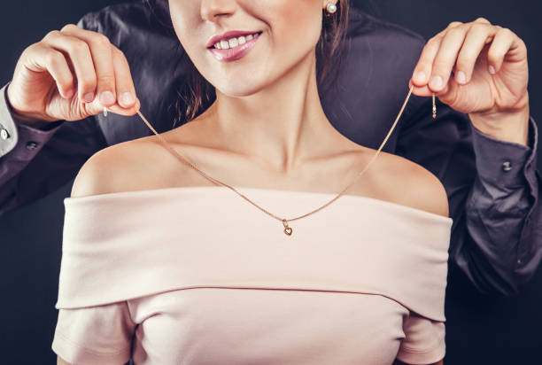man helping his girlfriend to try on a golden necklace. gift for valentines day. - ожерелье стоковые фото и изображения