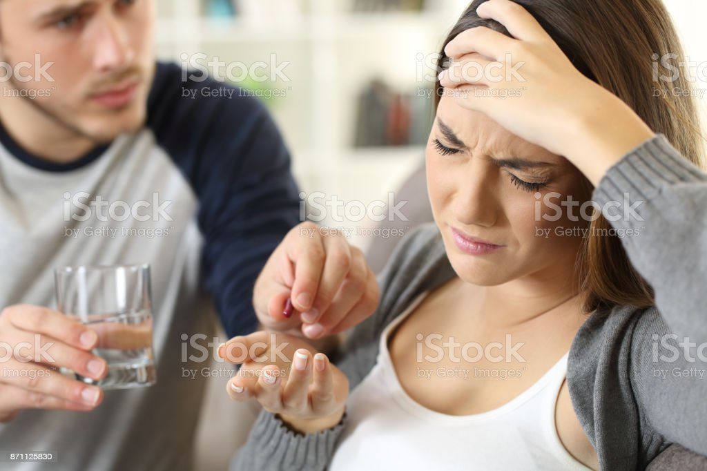 Man helping his ill wife giving medicine stock photo