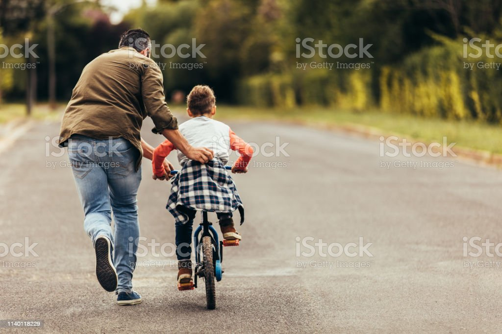 Man helping his kid in learning to ride a bicycle - Стоковые фото Близость роялти-фри