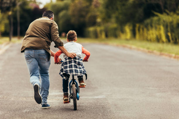 Man helping his kid in learning to ride a bicycle Rear view of a boy riding a bicycle while his father runs along holding the kid. Father teaching his son to ride a bicycle. father stock pictures, royalty-free photos & images
