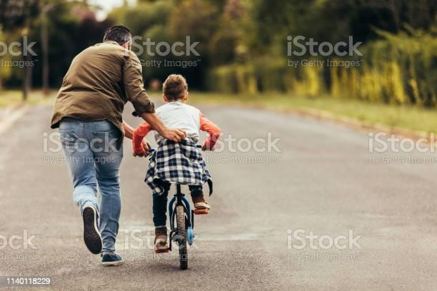 Man Helpt Zijn Kind In Het Leren Om Een Fiets Te Rijden Stockfoto en meer beelden van Alleenstaande vader