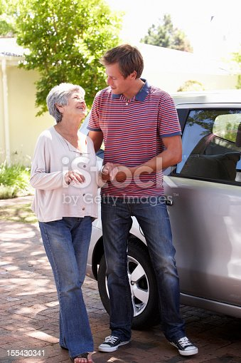 istock Man Helping Senior Woman Into Car 155430341