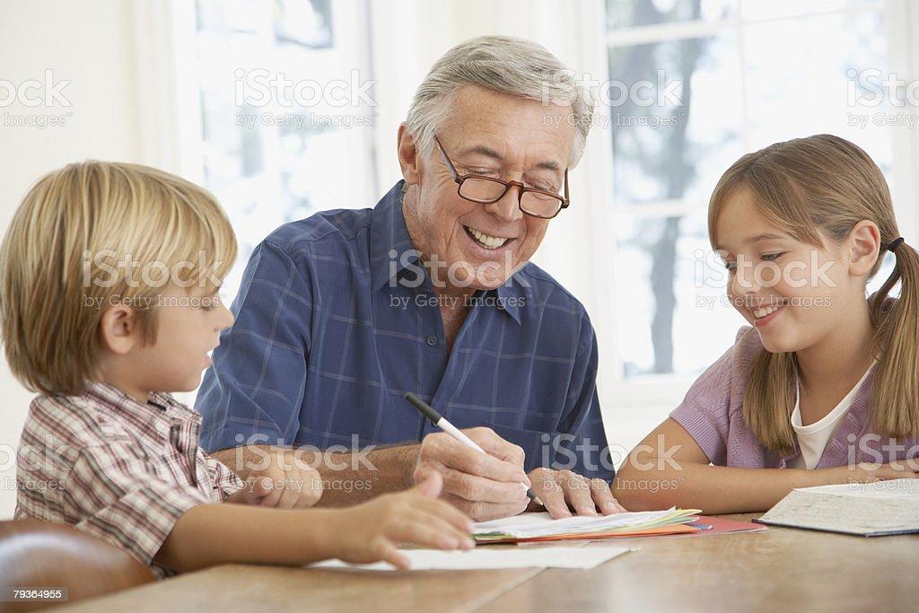 Man している 2 人の子供に宿題「キッチンテーブル」 ロイヤリティフリーストックフォト