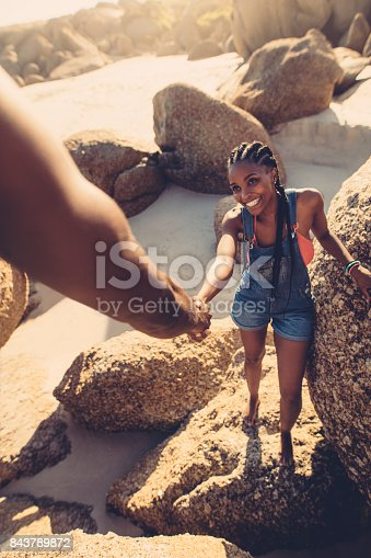 istock Man helping woman climbing rock at the beach 843789872