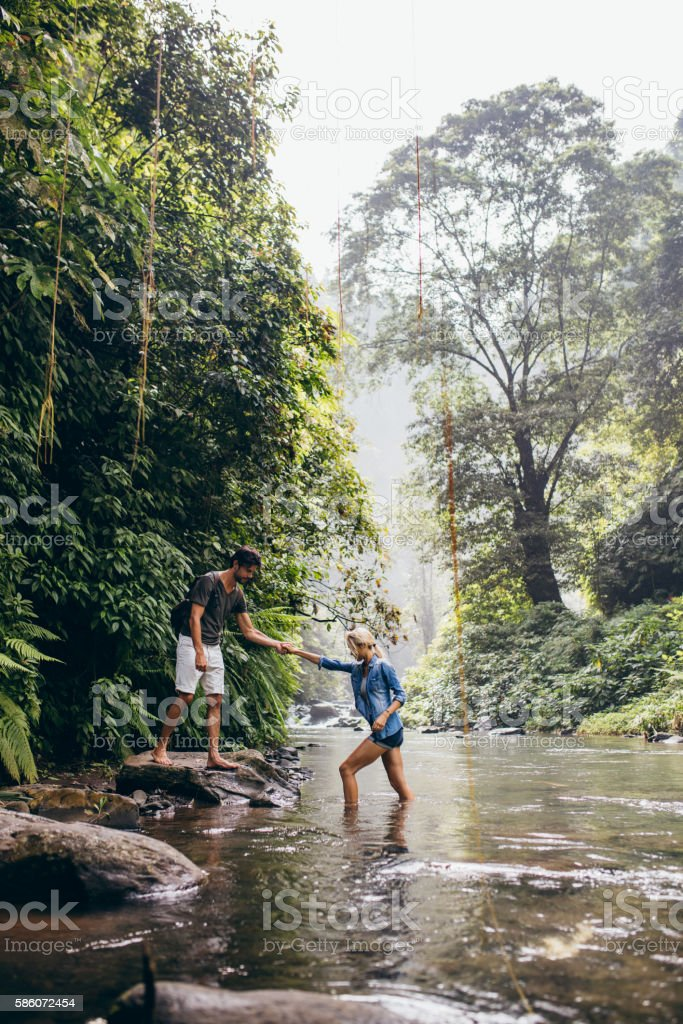 Man helping woman crossing stream stock photo