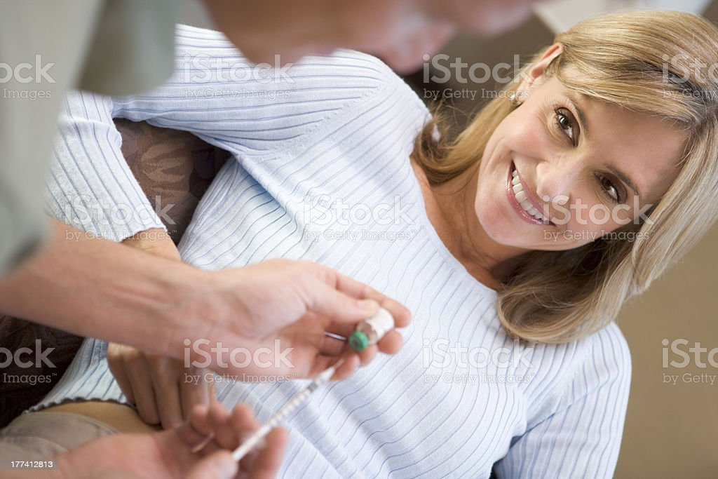 Man helping woman inject drugs to prepare for IVF treatment stock photo