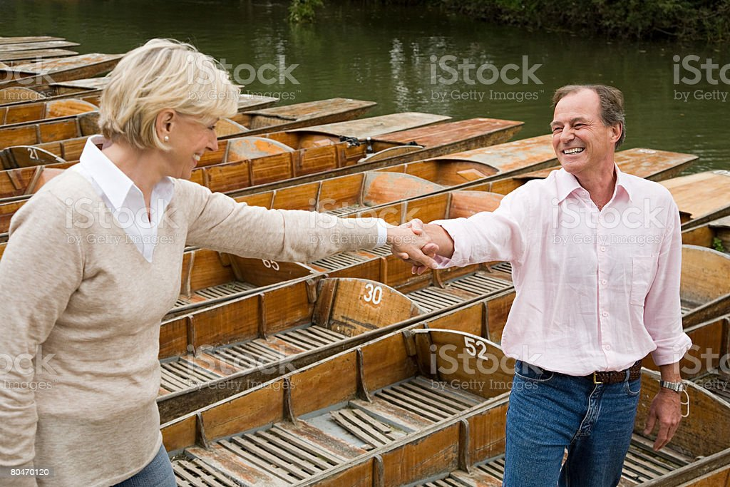 Man helping woman on to rowboat 免版稅 stock photo