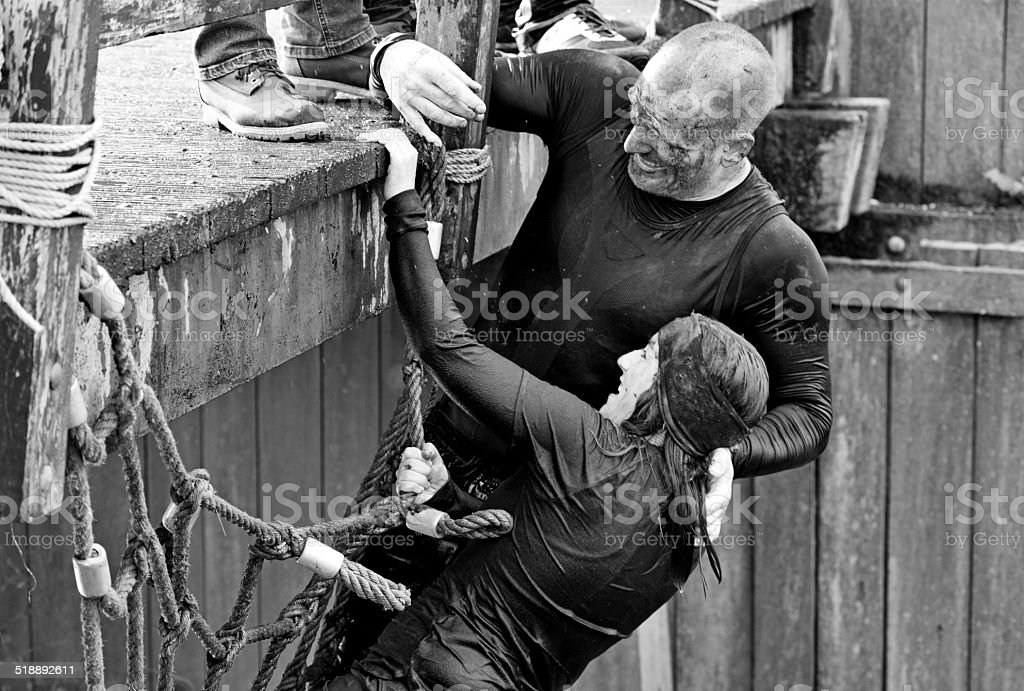 man helping woman to climb a net during obstacle run stock photo