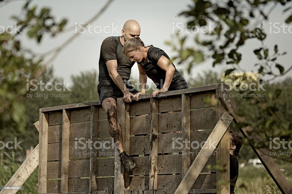 man helping woman to climb wooden wall obstacle stock photo