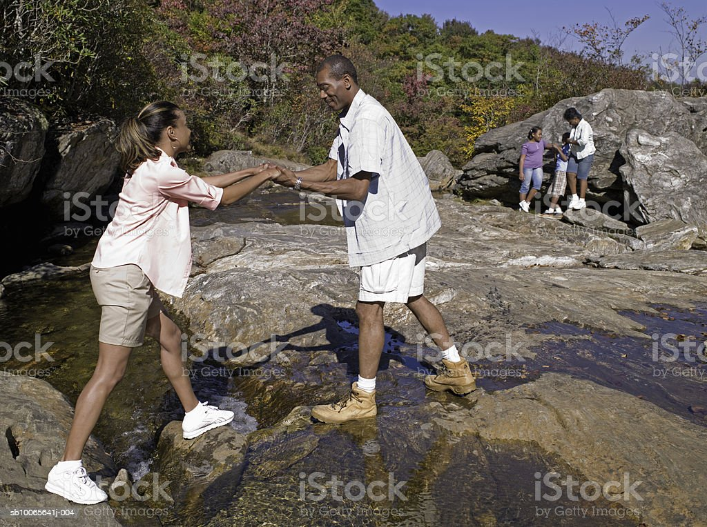Man helping woman to cross stream, grandmother with children (10-13) in background 免版稅 stock photo