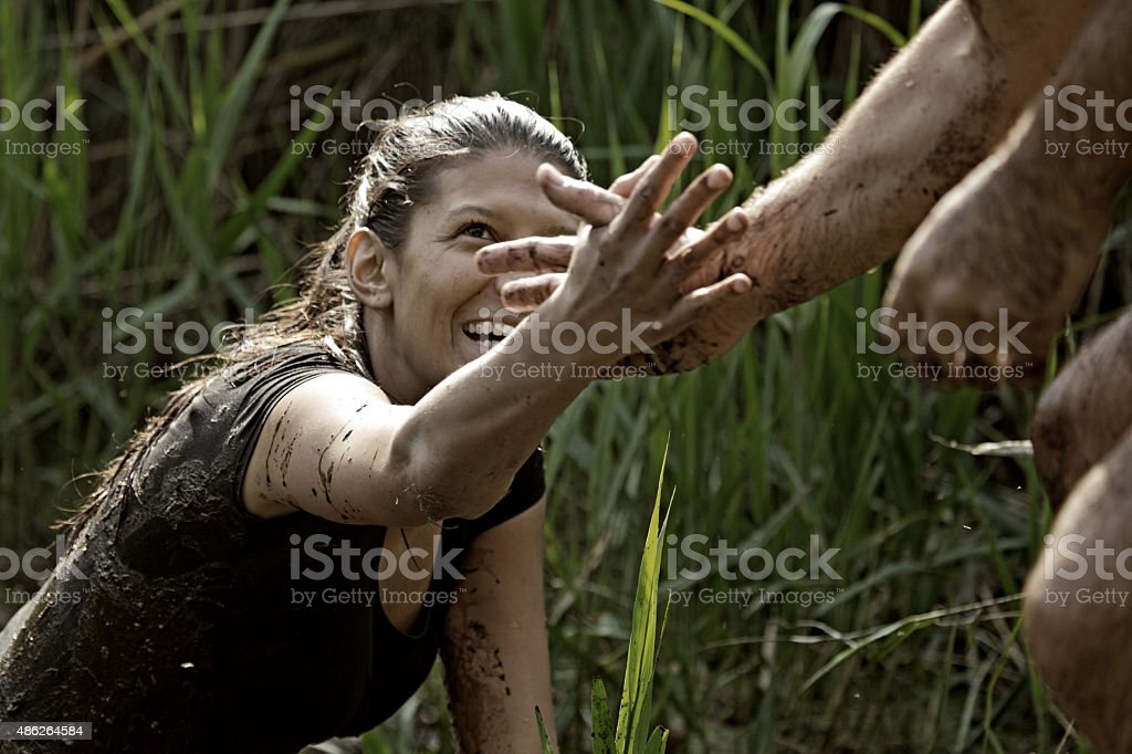 man helping woman to get out of canal stock photo