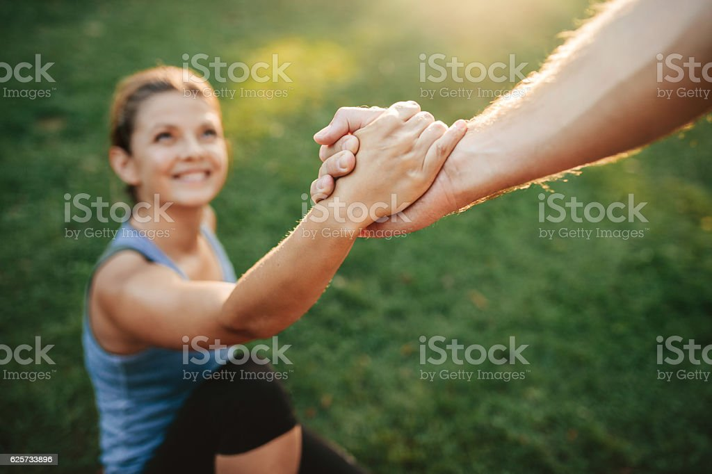 Man helping woman to stand up stock photo