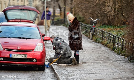 104275470istockphoto Man helping woman with car tire puncture 627759606