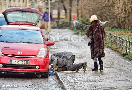 104275470istockphoto Man helping woman with car tire puncture 627760136