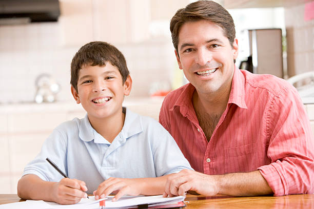 Man helping young boy in kitchen doing homework stock photo