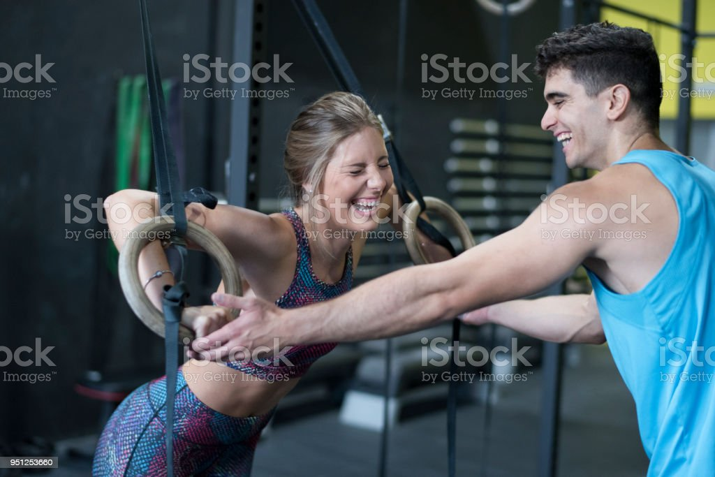 Man helps laughing  woman with ring training with complicity stock photo