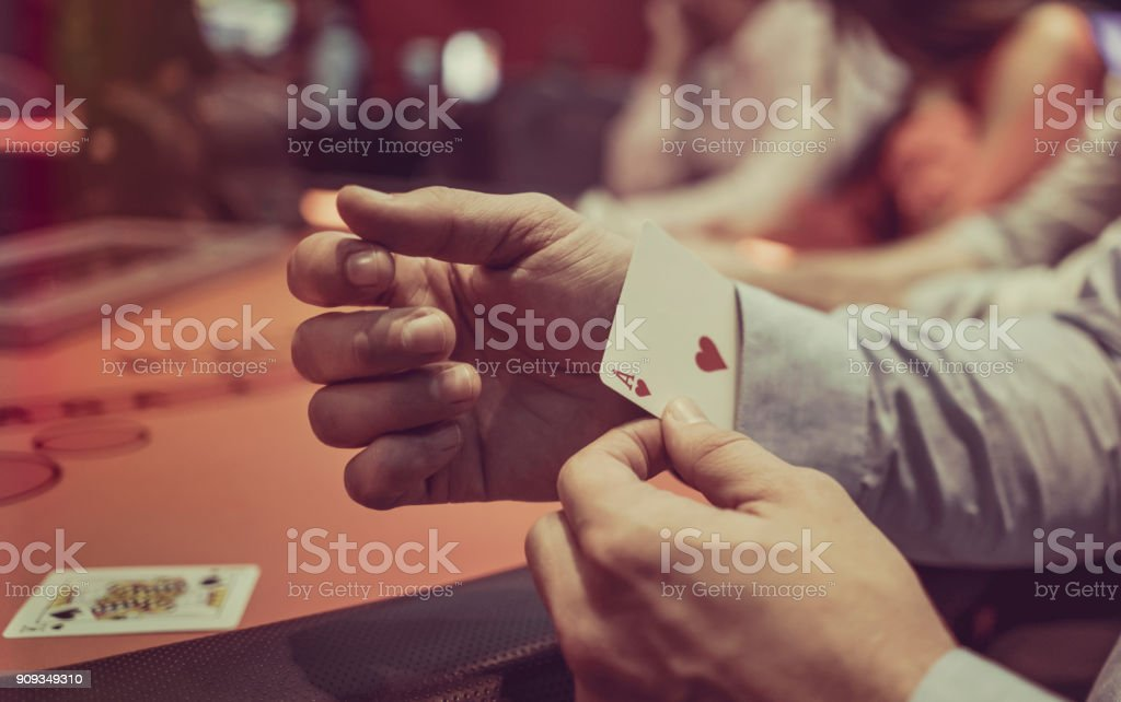 Man hiding an ace under in his sleeve at the casino stock photo