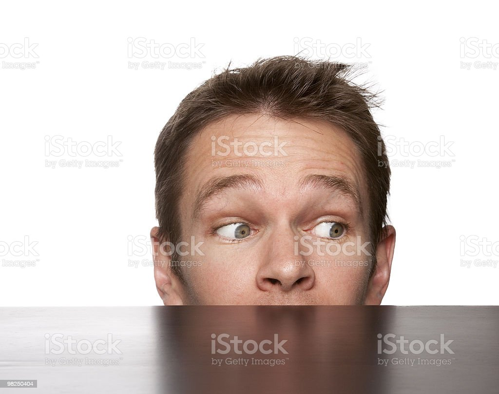 man hiding behind desk stock photo