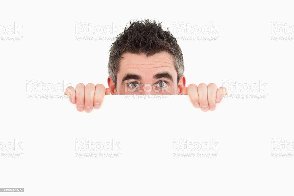 Man hiding behind white board stock photo