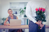 Close up of man hiding bouquet in front of businesswoman at office desk
