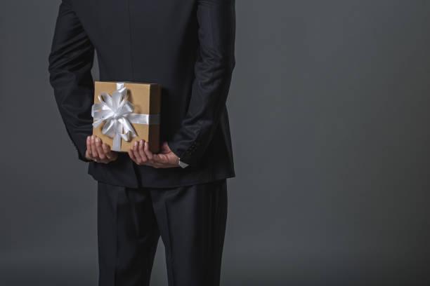 mann versteckt geschenk hinter rücken - besondere geschenke stock-fotos und bilder