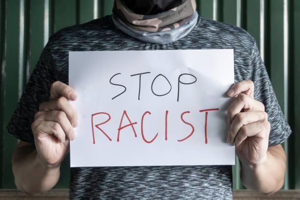 ein mann, der sein gesicht versteckt und ein zeichen antidiskriminierungsbotschaft in der hand hält. gleichheit in der menschheit obwohl unterschiedliche nationalitäten konzept. schluss mit rassismus, sollten alle in der gesellschaft gleich sein. - antidiscrimination stock-fotos und bilder